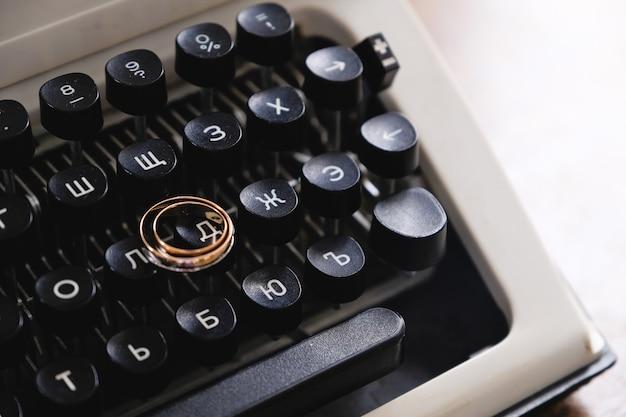 Obrączki na maszynie do pisania. obrączki ślubne umieszczone na starożytnych przycisków do pisania maszyny do pisania.