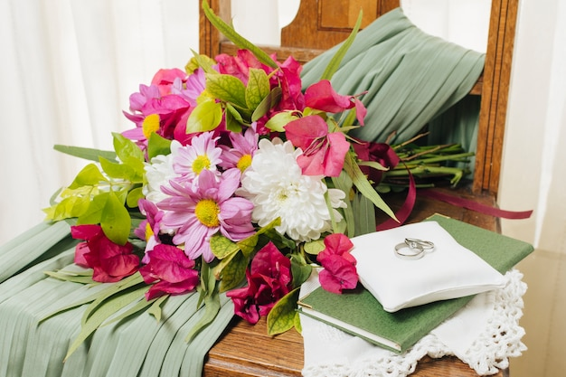 Obrączki na poduszce nad książką w pobliżu bukiet kwiatów i sukni ślubnej na krześle