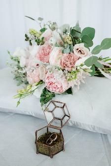 Obrączki są w drewnianym pudełku z płatkami kwiatów
