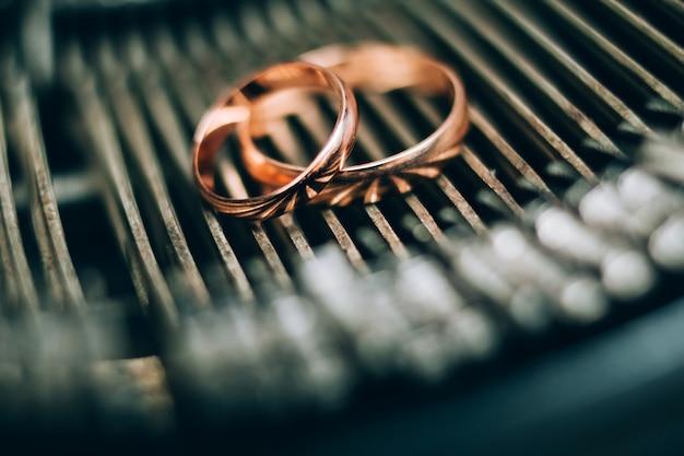 Obrączki ślubne. biżuteria z białego i żółtego złota. obrączka na powierzchni lustra.