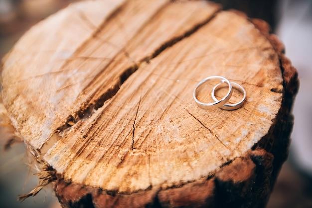 Obrączki ślubne. biżuteria z białego i żółtego złota. obrączka ślubna na drewnianej teksturze. drewniany kikut