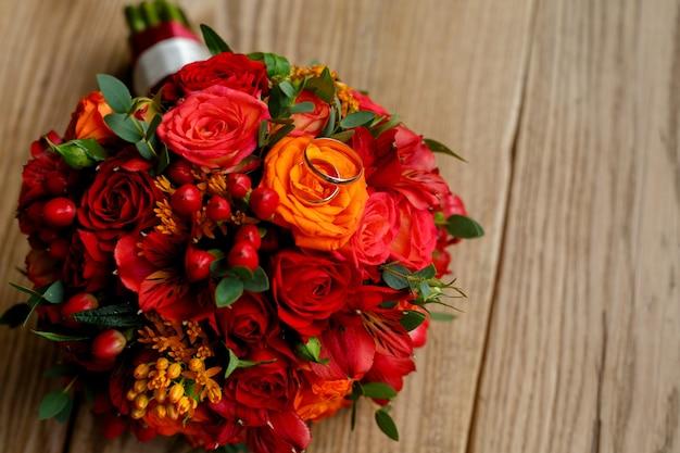 Obrączki ślubne i bukiet kwiatów na tle drewnianych