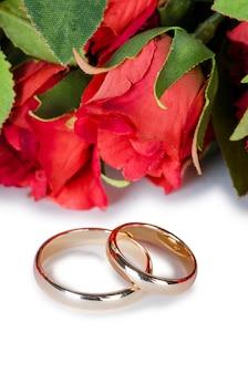 Obrączki ślubne i kwiaty na białym tle