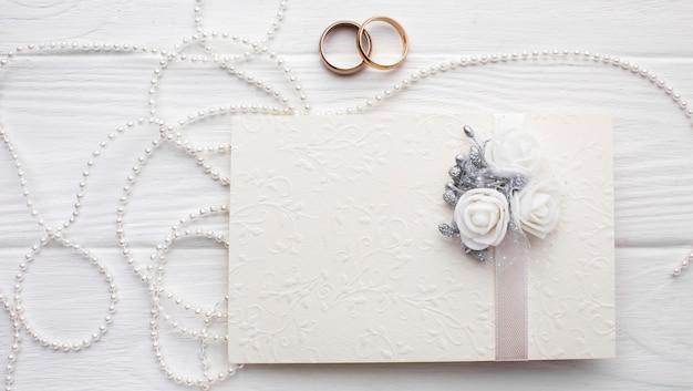Obrączki ślubne i peals z kopertą z zaproszeniem