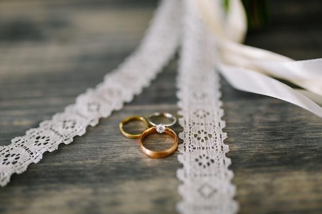 Obrączki ślubne i pierścionek panny młodej z kamieniem szlachetnym na szarym tle z wstążkami i