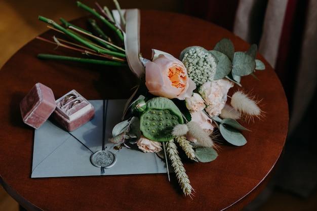 Obrączki ślubne, karta zaproszenie i piękny bukiet na okrągły drewniany stół kryty.