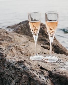 Obrączki ślubne, kieliszki, morze, szampan, kamienie, selektywne skupienie