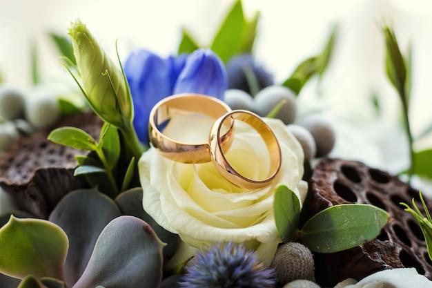 Obrączki ślubne leżą na bukiecie ślubnym