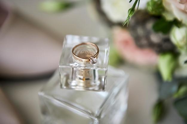 Obrączki ślubne leżą na butelce perfum