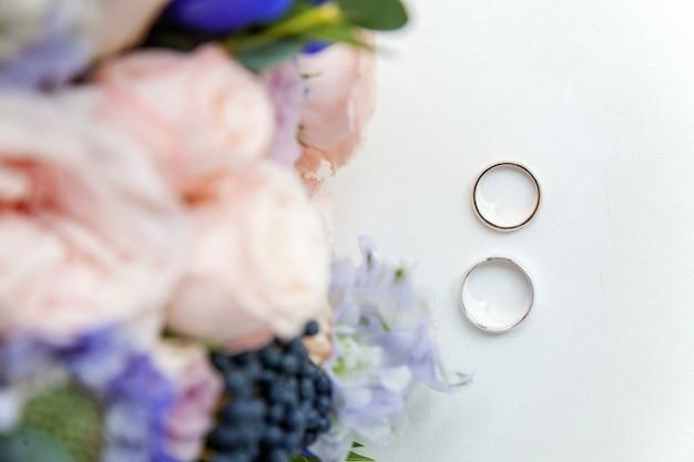 Obrączki ślubne leżą na drewnianej powierzchni bukietu kwiatów