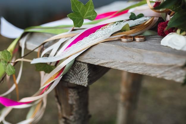 Obrączki ślubne leżą na drewnianym stole w pobliżu bukietu z wieloma wstążkami