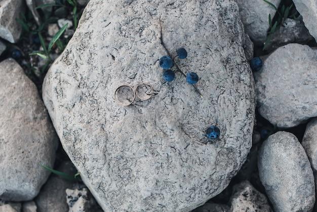 Obrączki ślubne leżą na kamieniu obok gałązki niebieskich jagód obrączek
