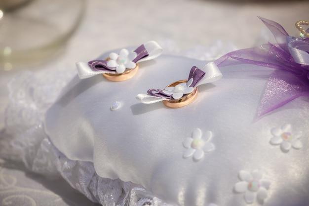 Obrączki ślubne leżą na małej poduszce