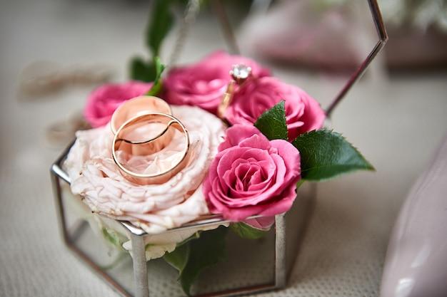 Obrączki ślubne leżą na pięknym bukiecie jako dodatki ślubne