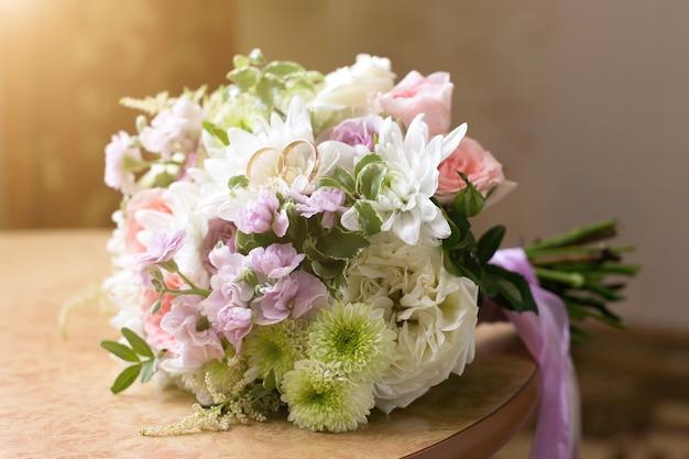 Obrączki ślubne leżą na płatkach bukietu ślubnego z kwiatów
