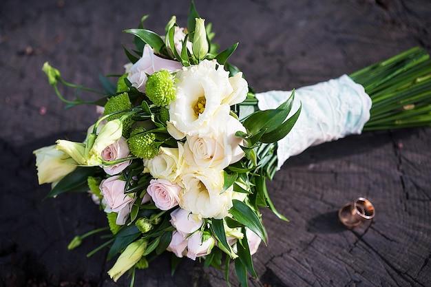 Obrączki ślubne leżą na pniu, w tle bukiet