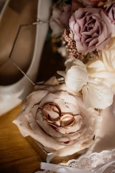 Obrączki ślubne leżą na róży