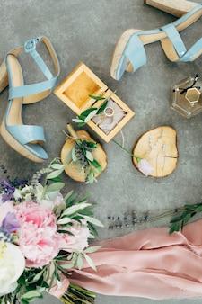 Obrączki ślubne leżą w drewnianym pudełku otoczonym sandałami na obcasach