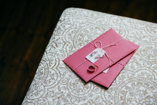 Obrączki ślubne leżące na różowym zaproszeniu