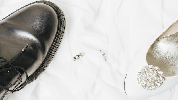 Obrączki ślubne między białymi szpilkami i czarnymi butami na szaliku