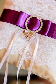 Obrączki ślubne na białej koronce i fioletowej wstążce