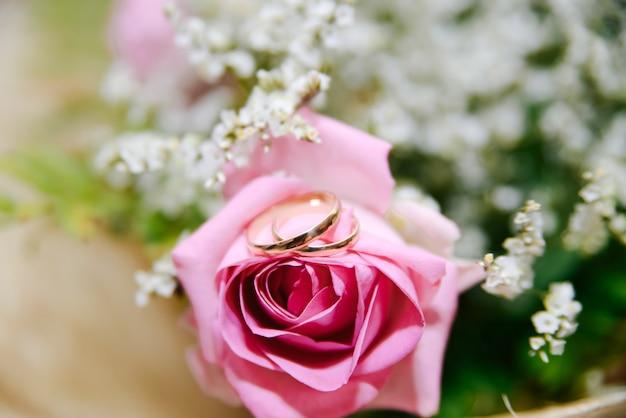 Obrączki ślubne na bukiecie różowi kwiaty, selekcyjna ostrość