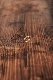Obrączki ślubne na ciemnym drewnianym tle.