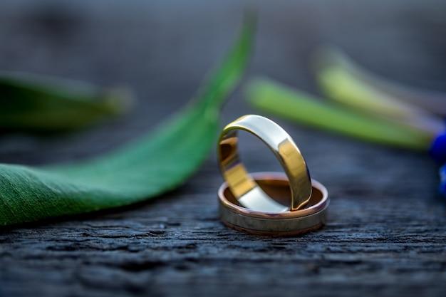 Obrączki ślubne na pięknym liściu rozgałęziają się i rocznik drewniany tekstury tło.