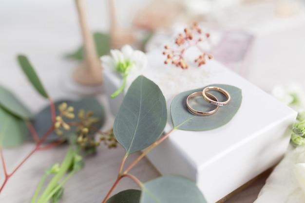 Obrączki ślubne na pięknym tle z akcesoriami ślubnymi
