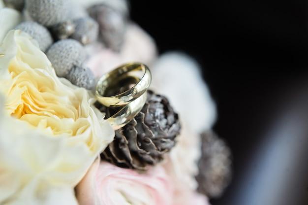 Obrączki ślubne na tle bukieta panny młodej