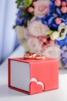 Obrączki ślubne na tle bukieta ślubnego