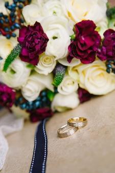Obrączki ślubne na tle bukietu kwiatów