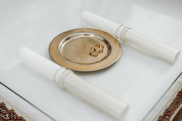 Obrączki ślubne na złotej tacy na białym stole