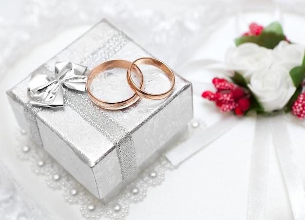 Obrączki ślubne, pudełko prezentowe i kwiaty dla panny młodej.