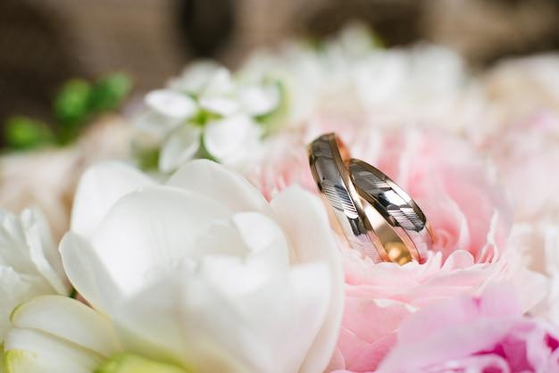 Obrączki ślubne w delikatnych ślubnych kwiatach zamykają up