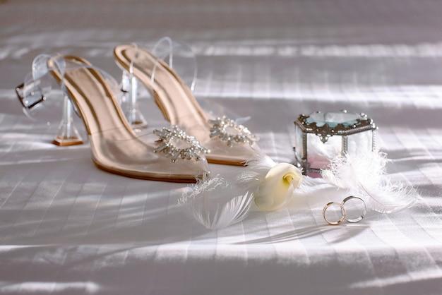 Obrączki ślubne z białymi piórkami obok szklanego pudełka i żółtym kwiatkiem obok beżowych butów panny młodej ozdobionych kamieniami na białym tle