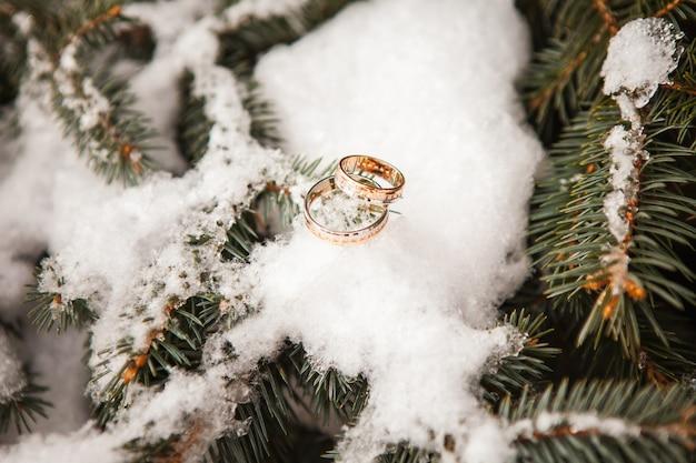 Obrączki ślubne z bliska na śniegu