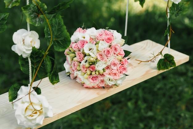 Obrączki ślubne z bukietem ślubnym leżące rano panny młodej.