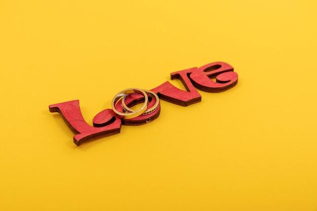 Obrączki ślubne z drewniane słowo miłość na żółtym tle. koncepcja valentine.