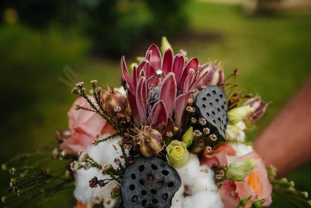 Obrączki ślubne zbliżenie na piękny ślubny bukiet podczas zmierzchu.