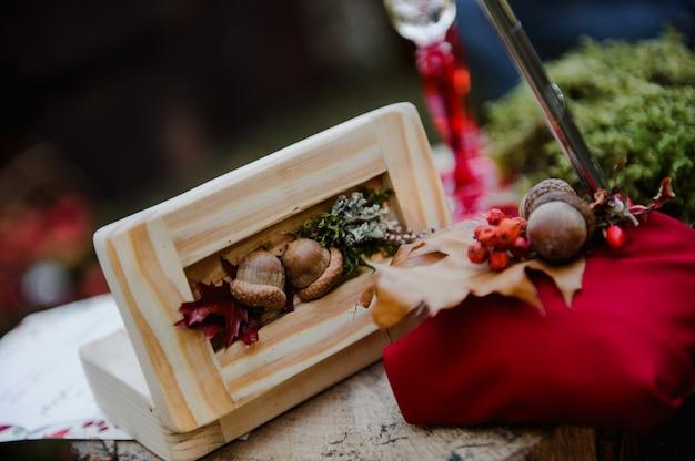 Obrączki w drewnianym pudełku z żołędziami. ślub. pierścienie na pniu.