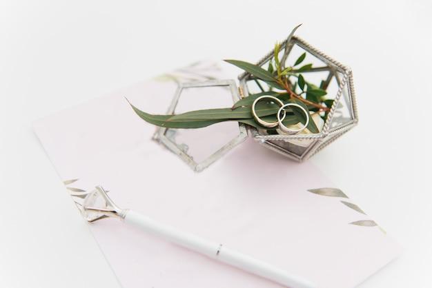 Obrączki w pudełku z kwiatami, wystrojem i szczegółami ceremonii ślubnej