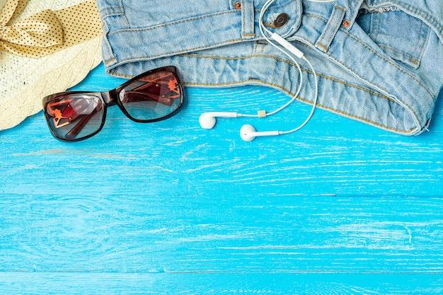 Obramia eleganckie żeńskie kapeluszowe cajgów okularów przeciwsłonecznych słuchawki na błękitnym drewnianym tle, copyspace, wakacje.