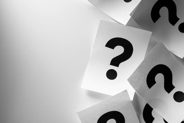 Obramowanie drukowanych znaków zapytania na białych kartach lub papierze w przypadkowym rozrzuceniu na stopniowanym białym tle