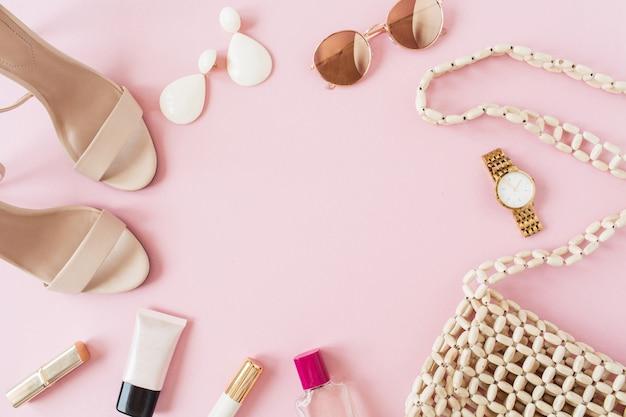 Obramowanie ramki wykonane z letniej kompozycji mody z kobiecymi dodatkami na różowej powierzchni