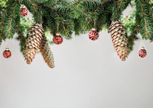 Obramowanie świąteczne dekoracje wykonane z gałęzi świerkowych, szyszek jodły i czerwonych błyszczących kulek na białym tle