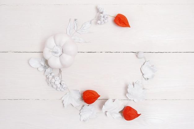 Obramuj białą dynię, jagody i liście na drewnianej jesieni