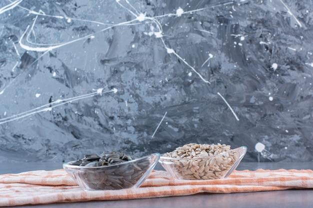 Obrane i nieobrane nasiona słonecznika w miseczkach na ściereczce, na marmurowej powierzchni