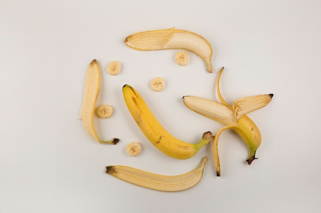 Obrane i pokrojone banany na białym tle, widok z góry