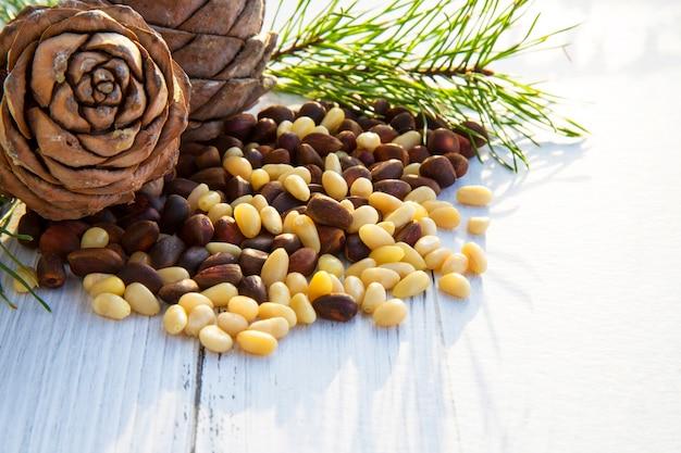 Obrane jądra orzechów cedrowych w łyżce, dwie szyszki sosnowe, zielone gałązki i orzechy w łupinie na ciemnej drewnianej desce
